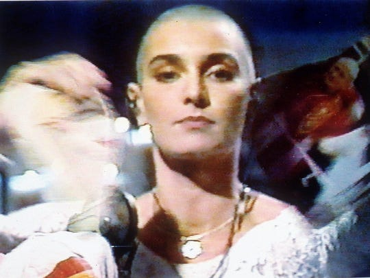 "Sinead O'Connor tears up a photo of Pope John Paul II on Oct. 3,1992, during a live appearance in New York on NBC's ""Saturday Night Live,"" in this frame grab. The incident took place after a song about racism, class differences, child abuse and other topics."
