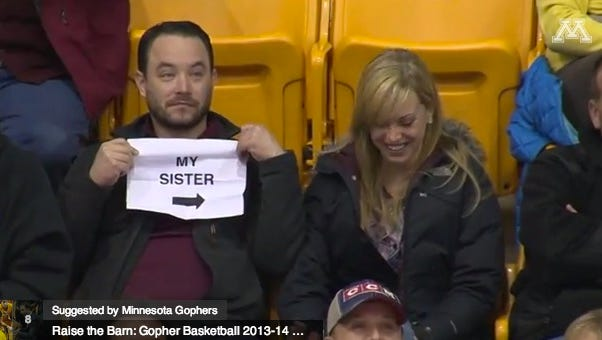 """Man at University of Michigan hockey game holds a sign with words """"MY SISTER"""" on it."""