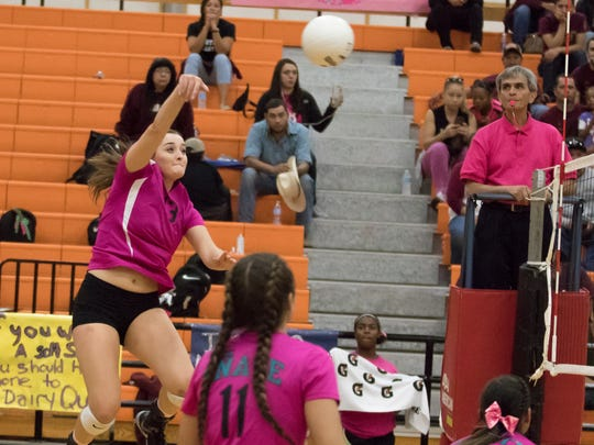 The Oñate High School volleyball team wears pink jerseys