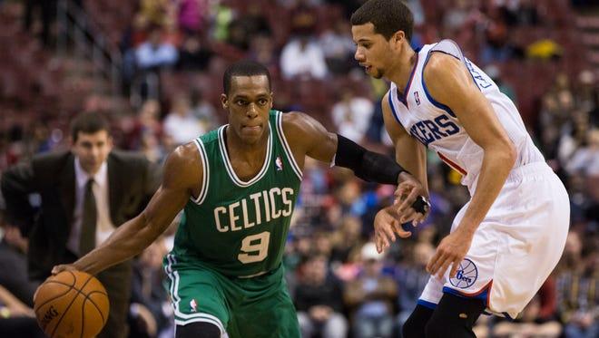 Boston Celtics' Rajon Rondo, left, looks to make his move on Philadelphia 76ers' Michael Carter-Williams, right during the second half of an NBA basketball game, Wednesday, Feb. 5, 2014, in Philadelphia.