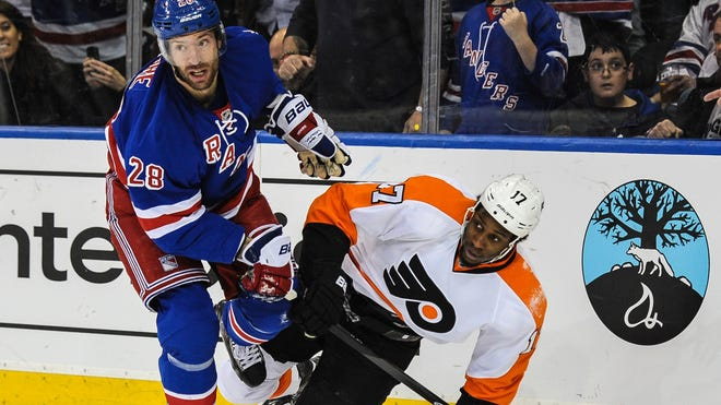 New York Rangers center Dominic Moore (28) and Philadelphia Flyers right wing Wayne Simmonds (17) battle in the corner in the third period.