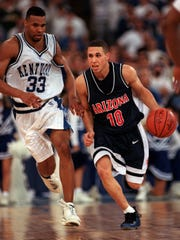 UA guard Mike Bibby is bringing the ball up the court with Kentucky player Ron Mercer, on the left chasing him during the NCAA Final Four Championship game in Indianapolis. – Arizona Daily Star photo