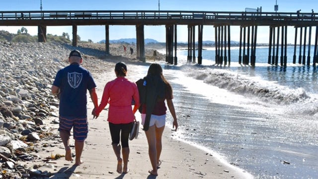 Patrick Tafoya, his wife, Rachel and their daughter, Katherine, stroll on the beach. Their rented home burned in the Thomas Fire. They say the ocean is their therapy.