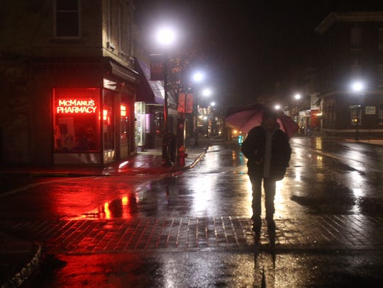 A pedestrian walks through freezing rain on Main Street