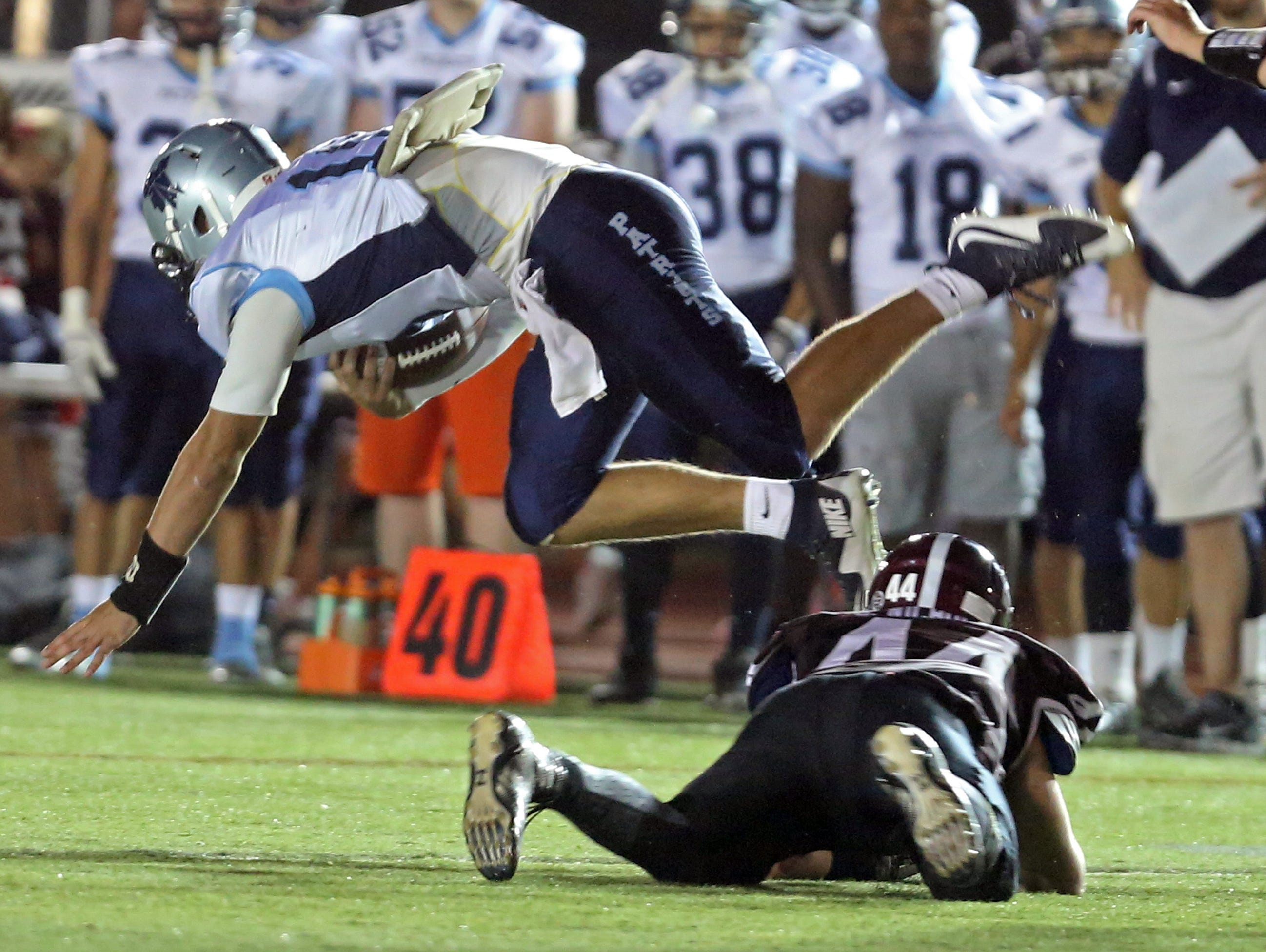 ]ohn Jay East Fishkill quarterback Ryan Schumacher flies over Scarsdale's Stephen Nicholas during a varsity football game at Scarsdale High School Sept. 25, 2015. John Jay defeated Scarsdale 36-14.