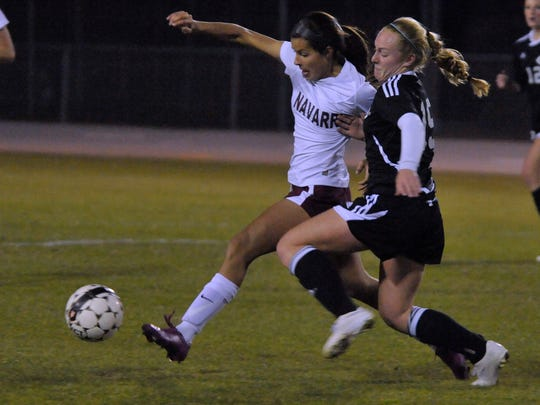 Emily Madril (in white uniform) races after the ball against a member of the Creekside High Knights during their Region 1-4A title game at Navarre in 2015.