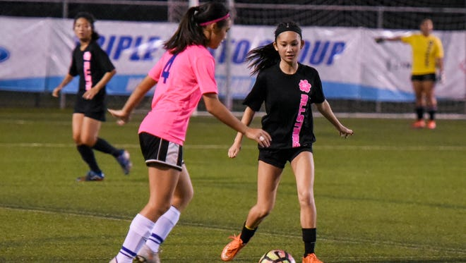 Team Magahaga's Hallie Wigsten (4) goes toe-to-toe with Team Metgot's Chloe Miranda during their Girls High School All-Star Invitational matchup at the Guam Football Association National Training Center in Dededo on Thursday, may 24, 2017.