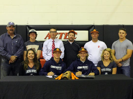 Aztec High School graduates Jake Taylor, bottom row, second from left, and Beau Crawford, second from right, sign their national letters of intent on Monday at Aztec High School, surrounded by their relatives and coaches. Both students will play baseball at Concordia University in Seward, Neb.