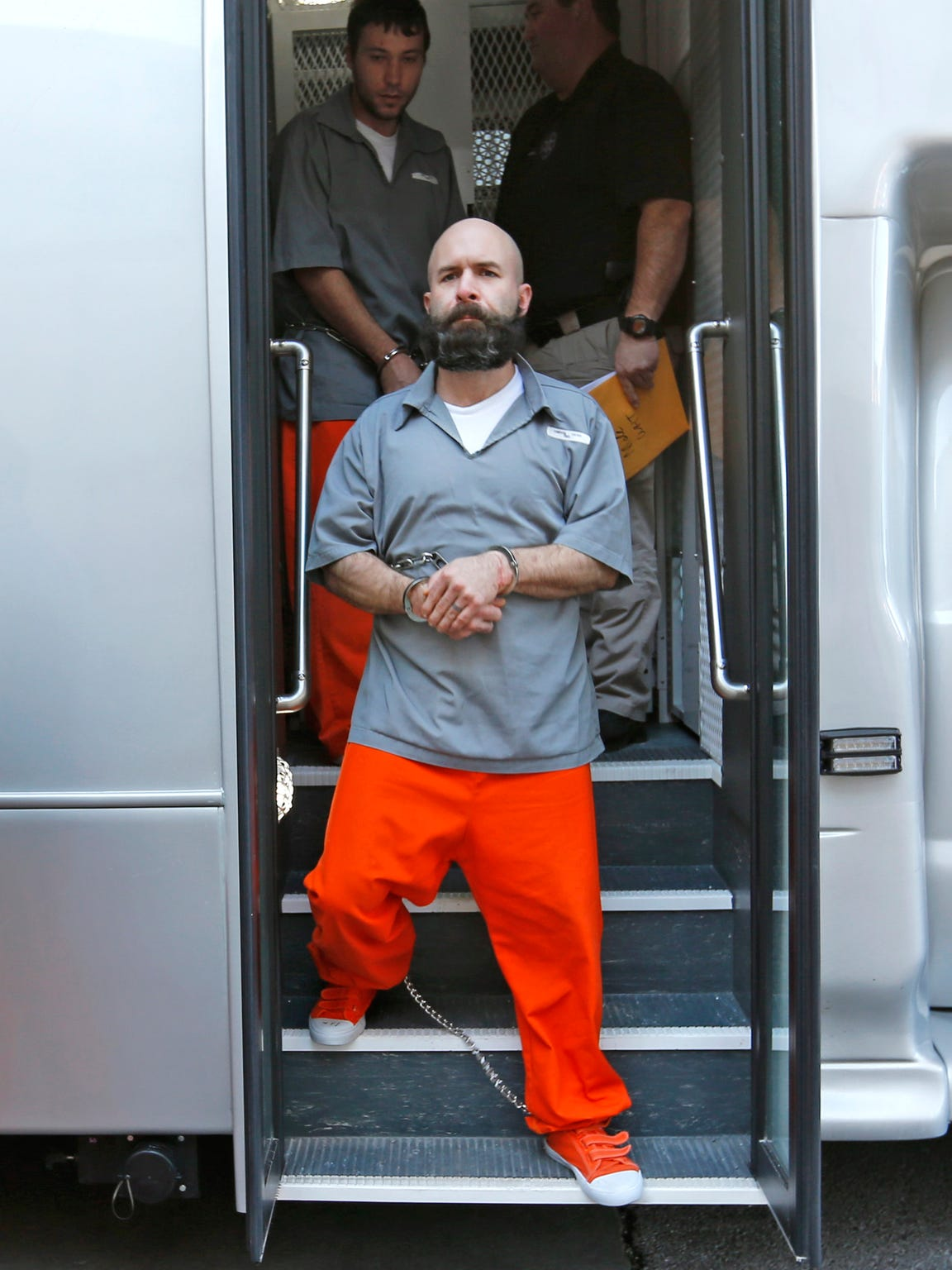 Prisoners step off the bus while being escorted into