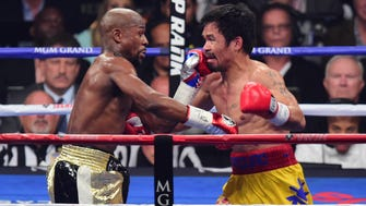 May 2, 2015; Las Vegas, NV, USA; Floyd Mayweather (black/gold trunks) and Manny Pacquiao (yellow/red trunks) box during their world welterweight championship bout at MGM Grand Garden Arena. Mayweather won via unanimous decision. Mandatory Credit: Joe Camporeale-USA TODAY Sports ORG XMIT: USATSI-222852 ORIG FILE ID:  20150502_jla_aa9_309.jpg