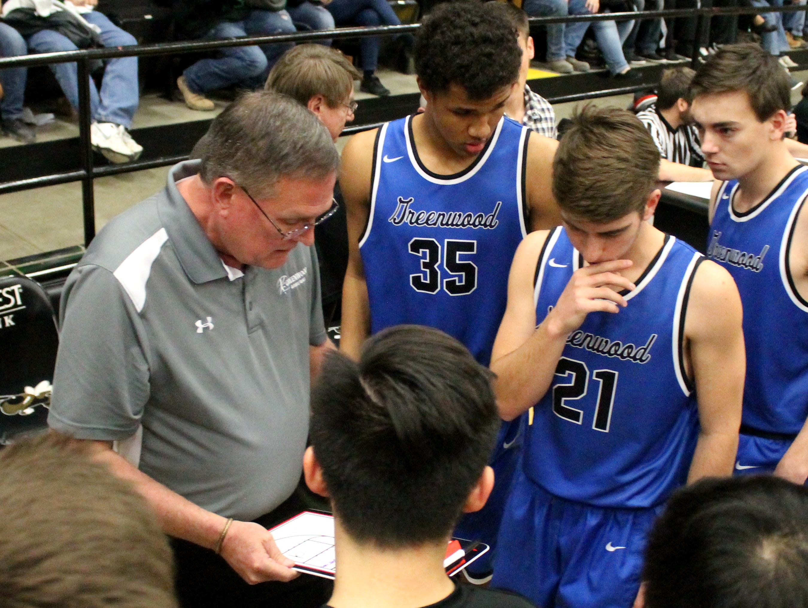 Greenwood boys basketball coach Darren Taylor (in grey) talks strategy with the Blue Jays before a Class 2 sectional playoff game at Lebanon against Iberia March 1, 2017.