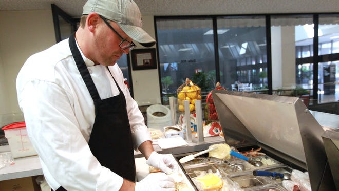 Kristoffer Busk prepares a sandwich at Shoreline Sandwich Co. in the Bank of America lobby.