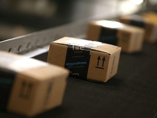 Boxes move along a conveyor belt at an Amazon fulfillment