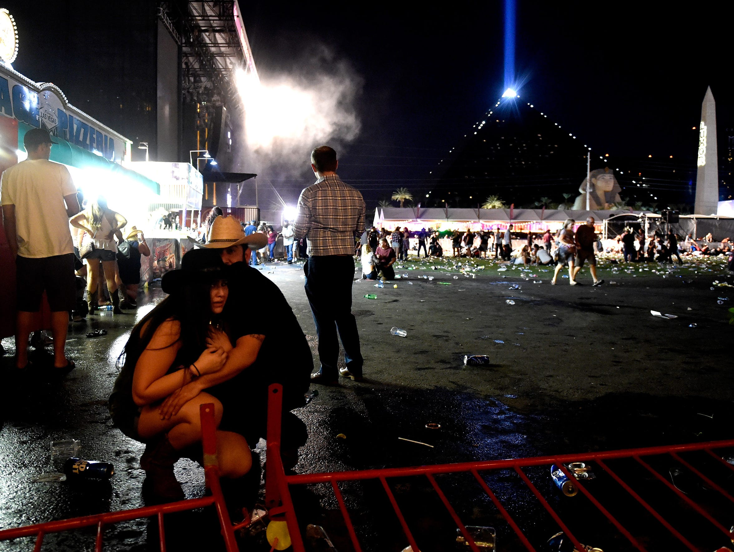 People take cover at the Route 91 Harvest country music festival.