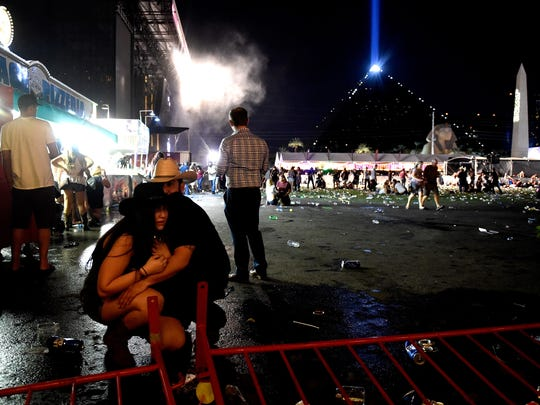 People take cover at the Route 91 Harvest country music festival after a gunman opened fire on the concert on Oct. 1, 2017, in Las Vegas.