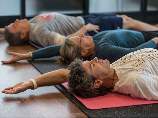 Brian Bocker of Avon-by-the-Sea, bottom, stretches out with Dan (top) and Mary Kiningham of Little Siver. Kyle Kim of Integrative Wellness Group holds a class teaching people proper foundation of exercise. Belmar, NJWednesday, November 15, 2017@dhoodhood