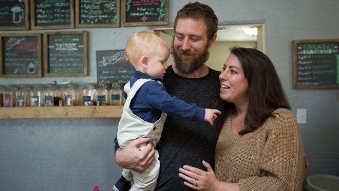 Arianna Parsons, right, with her husband Tyrell Thacker and their 10-month-old son, Thomas have a chat in the front room of their business, Beck's Roasting House and Creamery, Wednesday January 10, 2018.