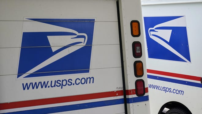 """Mail delivery vehicles are parked outside a post office in this Associated Press photo. The postmaster general announced Tuesday he is halting some operational changes to mail delivery that critics warned were causing widespread delays and could disrupt voting in the November election. Postmaster General Louis DeJoy said he would """"suspend"""" his initiatives until after the election """"to avoid even the appearance of impact on election mail."""""""