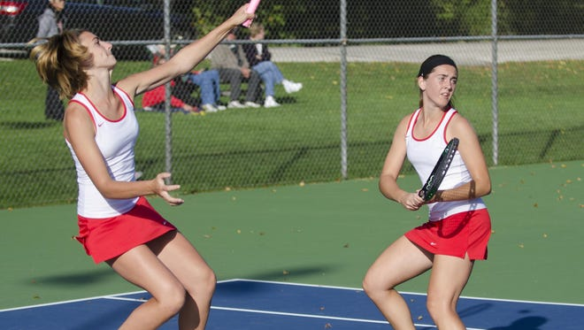 Manitowoc Lincoln's Sydney Verbauwhede, left, smacks an overhead smash as partner Jen Belisle looks on in their No. 1 doubles match against Pulaski on Tuesday at Lincoln Park.