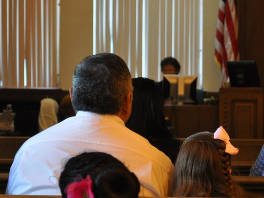 Ernie Carrasco sits with his soon to be adopted daughter at the Eddy County Courthouse during the National Adoption Day celebration.