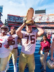 Florida State players celebrate with the gator head