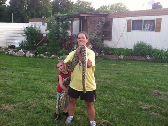 Treasa Trexel poses with her son's Burmese python.