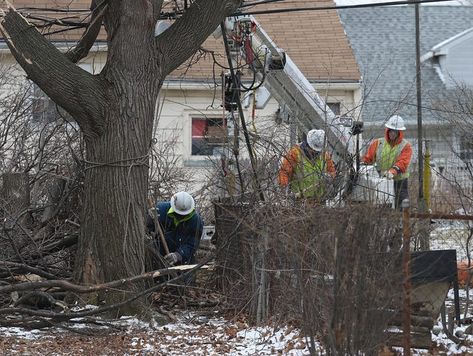A crew works on putting in a new pole in a backyard