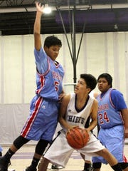 Mescalero's Matias Lapaz, right, drives to the basket while being heavily defended.