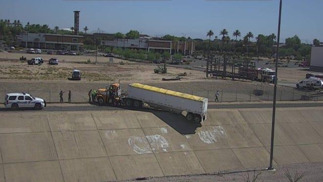 A semitruck hangs off an embankment along Interstate 10 in Avondale on June 12, 2017.