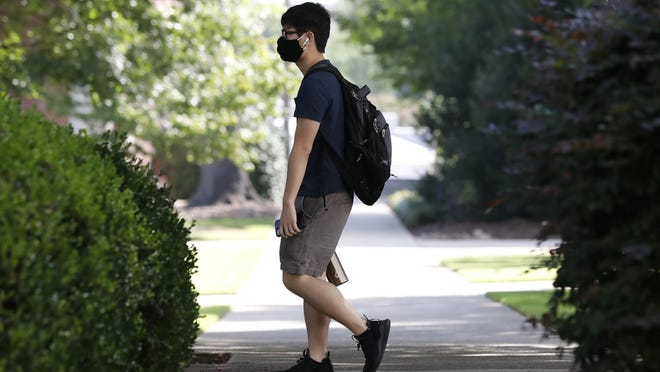 A student, wearing a mask, walks on campus at the University of Georgia, Thursday, Aug. 20, 2020. in Athens, Ga.