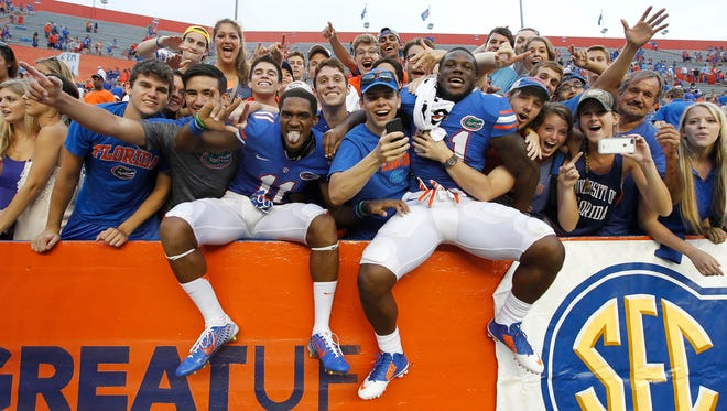 Florida wide receiver Demarcus Robinson (11) and running back Kelvin Taylor (21) celebrate with fans after they beat the Eastern Michigan Eagles at Ben Hill Griffin Stadium.