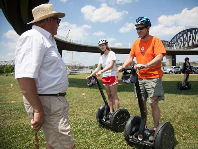 Owner Rob Reynolds with Segway of Louisville located at Wheel Fun Rentals talks to Maddy DuPlessis and her father Sam DuPlessis under the walking bridge at Waterfront Park. June 6, 2014