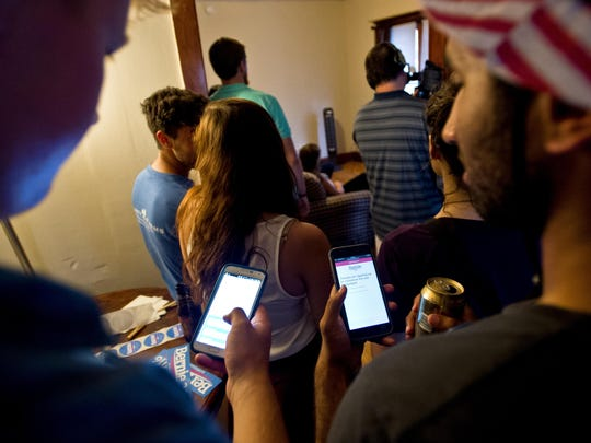From left, UVM juniors Graham Wright and Aditya Vangala check into the Bernie Sanders campaign mobile site on their smart phones after watching Sen. Bernie Sanders speak via a live video stream Wednesday night. About 20 students and supporters of Sanders watched at a house party on Isham Street in Burlington, joining more than 100,000 nationally who signed up to view the online broadcast.