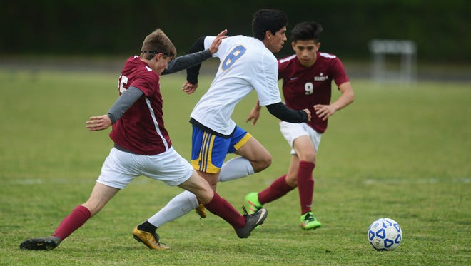 Northampton's Arturo Gildo (8) splits a pair of Nandua defenders during their game in Eastville, Va. on Wednesday, April 27, 2016. Northampton won the game 2-1.