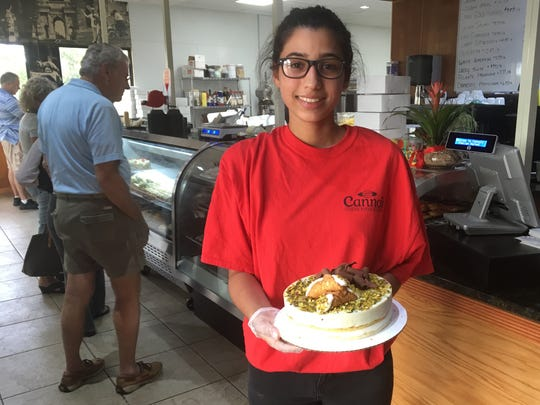 Elliana Ferrara holds a cannoli cake made with pistachio cream and shaved chocolate at Cannoli Italian Market and Bakery in south Cape Coral.