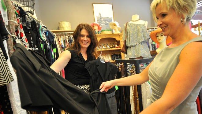 Owner Brenda Schumacher, left, helps her customer Becky Schemenauer Thursday afternoon at Second Peek Boutique in downtown Wausau.