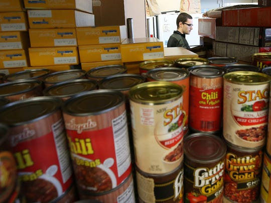 Volunteer Andrew D'Ambruoso is framed by nonperishables stacked on a shelf Friday at the North Kitsap Fishline in Poulsbo.
