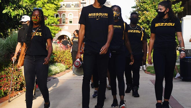 Missouri Black Student Athlete Association members, led by Cason Suggs, center, the president of Mizzou Black Student Athlete Association, take the first few steps of their march on Wednesday evening.