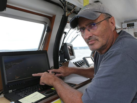 John Lipscomb, boat captain for Riverkeeper, points