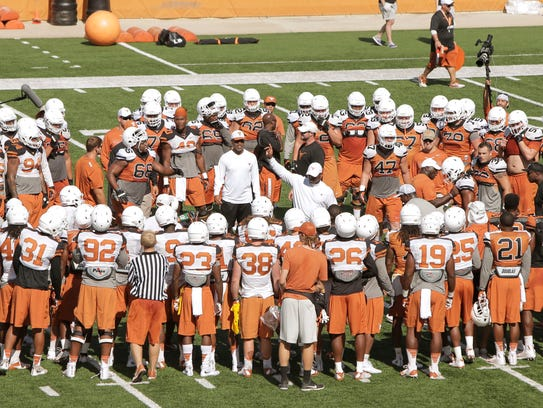 Charlie Strong (center) talks to his team during the