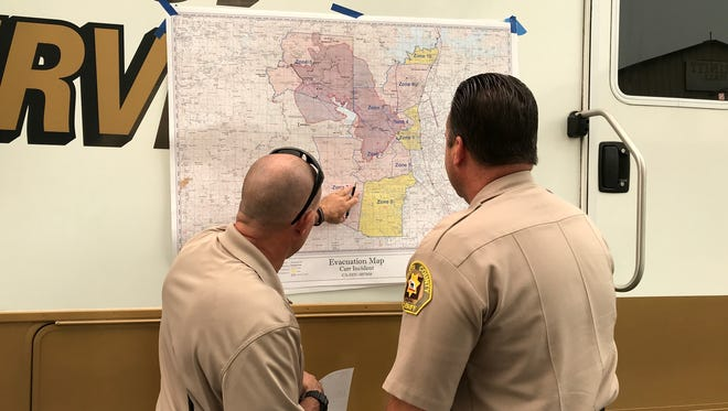 Two Shasta County sheriff's deputies check the Carr Fire evacuation map this week at the command center at the Shasta District Fair grounds in Anderson. More residents were being let back in to their homes in previously evacuated areas