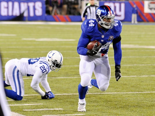 New York Giants running back Andre Williams (44) runs away from Indianapolis Colts' Darius Butler (20) for a touchdown during the second half of an NFL football game Monday, Nov. 3, 2014, in East Rutherford, N.J. (AP Photo/Bill Kostroun)