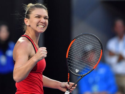 Romania's Simona Halep celebrates after defeating Canada's Eugenie Bouchard in their second round match at the Australian Open tennis championships in Melbourne, Australia, Thursday, Jan. 18, 2018. (AP Photo/Andy Brownbill)