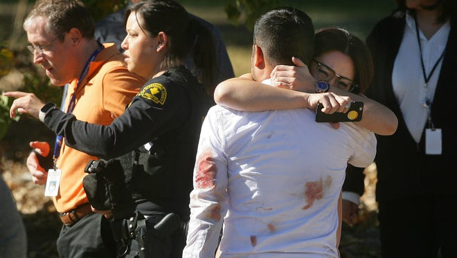 A couple embraces following a shooting that killed multiple people at a social services facility on Wednesday in in San Bernardino, Calif.