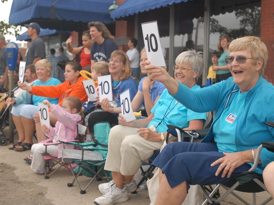 Nancy Madtes, of Lansing, right, Joan Westphal, of Port Huron, and the female members of their family rate the entries in the Rotary International Day Parade.