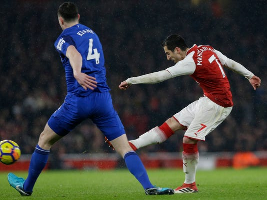 Arsenal's Henrikh Mkhitaryan, right, shoots at goal watched by Everton's Michael Keane during the English Premier League soccer match between Arsenal and Everton at the Emirates stadium in London, Saturday, Feb. 3, 2018. (AP Photo/Alastair Grant)