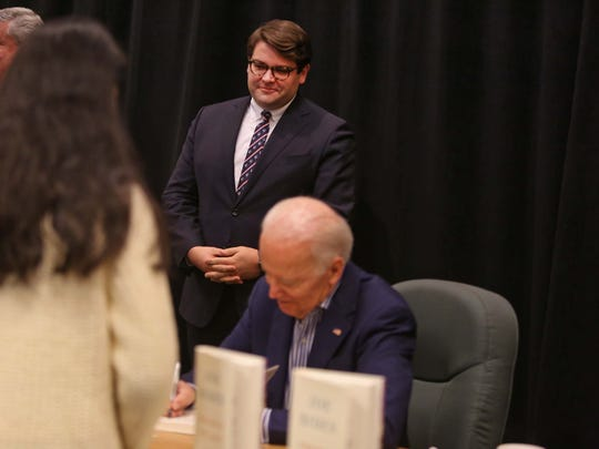 "Bill Russo, communications director for former Vice President Joe Biden watches over him as he signs copies of his new book, ""Promise Me, Dad: A Year of Hope, Hardship, and Purpose,"" at the Barnes & Noble at Concord Mall."