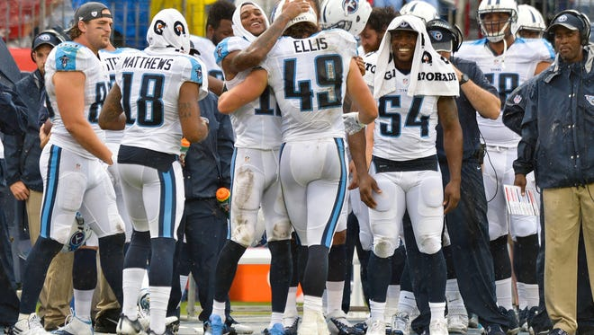 Tennessee Titans tight end Alex Ellis (49) is congratulated by Titans wide receiver Tajae Sharpe (19) and other teammates on the sideline after scoring touchdown against the Carolina Panthers during the second half at Nissan Stadium.