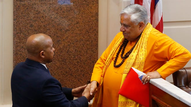 """Universal Society of Hinduism President Rajan Zed, right, talks with Oklahoma state Sen. Kevin Matthews, left, D-Tulsa, after delivering a prayer to start the day in the Oklahoma Senate in Oklahoma City, Monday, April 30, 2018. On July 28, Zed protested a Springfield Brewing Co. beer label that features a depiction of the Hindu deity Lord Ganesha, calling it """"highly inappropriate."""""""