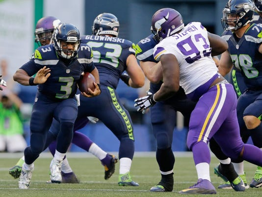 Seattle Seahawks quarterback Russell Wilson, left, runs the ball as Minnesota Vikings defensive tackle Shamar Stephen (93) closes in during the first half of a preseason NFL football game Thursday, Aug. 18, 2016, in Seattle. (AP Photo/John Froschauer)
